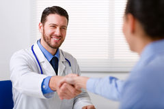 Doctor in white coat shake hand. Male doctor in white coat smiling while shaking hand to female colleague blurred in foreground Royalty Free Stock Images