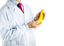 Doctor in white coat showing a banana Royalty Free Stock Photos
