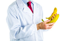 Doctor in white coat showing big and small bananas Royalty Free Stock Photos