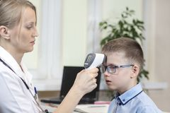 Doctor in a white coat and a stethoscope around the neck is sitting in the doctor`s office. He measures the temperature of the boy. In a blue shirt and glasses stock photo