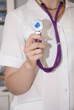Doctor in a white coat with a stethoscope prepared for the pati. A young doctor in a white coat with a stethoscope prepared for the patient Royalty Free Stock Photos