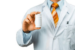 Doctor In White Coat With A Stethoscope On Shoulder Holding a Bottle Of Pills Between His Fingers. Healthcare Medical Hospital Con Stock Photo