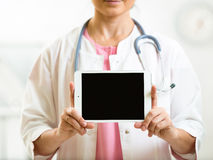 Doctor in white coat with stethoscope showing blank digit. Female doctor in white coat with stethoscope showing blank digital tablet pc Royalty Free Stock Photo