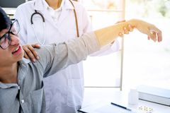 Doctor in white coat taking and checking the Patient`s wrist and royalty free stock image