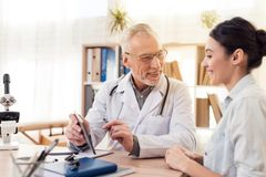 Doctor with stethoscope and female patient in office. Doctor is using tablet. royalty free stock images