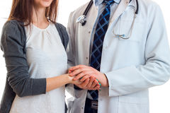A doctor in a white lab coat holding a young girl`s hand close-up Stock Photography