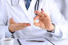 Doctor in a white  labcoat giving a pill Royalty Free Stock Photography
