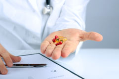 Doctor in a white labcoat giving  pills Royalty Free Stock Images