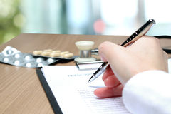 Doctor  in a white labcoat writing out RX prescription Stock Photography