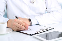 Doctor  in a white labcoat writing out RX prescription Royalty Free Stock Photo