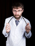 Doctor in a white medical robe, standing and holding a stethoscope Stock Photo