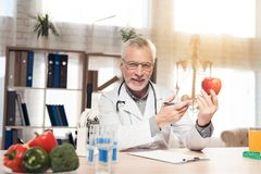 Doctor sitting at desk in office. Doctor is holding fresh red apple. royalty free stock photos