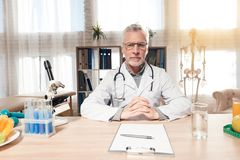 Doctor sitting at desk in office with microscope, stethoscope and clipboard. Doctor in white robe sitting at desk in office with microscope, stethoscope and Stock Photos