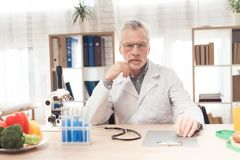 Doctor sitting at desk in office with microscope, stethoscope and clipboard. Doctor in white robe sitting at desk in office with microscope, stethoscope and Royalty Free Stock Photos