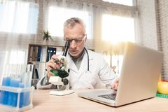 Doctor sitting at desk in office with microscope and stethoscope. Man is looking in microscope. Doctor in white robe sitting at desk in office with microscope Royalty Free Stock Photos