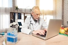 Doctor sitting at desk in office with microscope and stethoscope. Man is working on laptop. royalty free stock photography