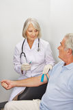 Doctor withdrawing blood from senior patient Royalty Free Stock Photo