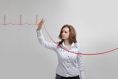 Doctor woman and cardiogram lines. Young doctor woman and cardiogram lines in air Stock Photo