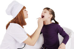 Doctor woman checking the throat of a young patient girl Royalty Free Stock Images