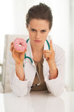 Doctor woman with donut threatening with finger Royalty Free Stock Images