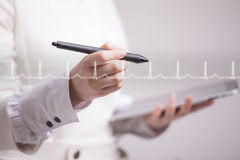 Doctor woman drawing cardiogram. Young doctor woman drawing cardiogram in air Stock Image