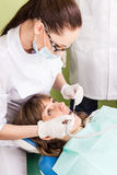 Doctor woman drills her patient tooth Royalty Free Stock Image