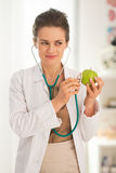 Doctor woman examining apple with stethoscope Stock Photos