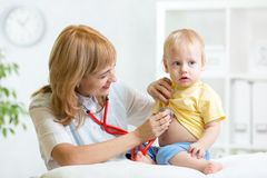 Doctor woman examining child boy with stethoscope Stock Photos