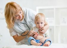 Doctor woman examining heartbeat of kid boy with. Doctor women examining heartbeat of little boy with stethoscope Stock Photo