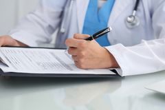 Doctor woman filling up medical form while sitting at the table, close-up of hands Stock Photos