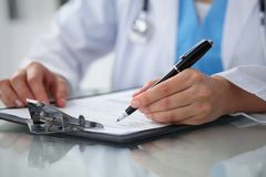 Doctor woman filling up medical form while sitting at the table, close-up of hands Royalty Free Stock Images
