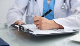 Doctor woman filling up medical form while sitting at the table, close-up of hands Royalty Free Stock Image