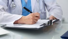 Doctor woman filling up medical form while sitting at the table, close-up of hands Stock Image