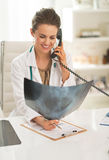 Doctor woman with fluorography talking phone Stock Images