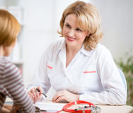 Doctor woman friendly talking to patient in her Stock Photos