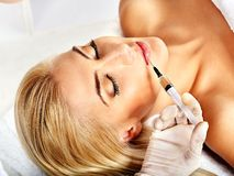 Doctor woman giving botox injections. Isolated stock photos