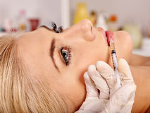 Doctor woman giving botox injections royalty free stock photography