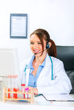 Doctor woman with headset working on computer Royalty Free Stock Photography
