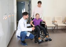 Doctor with woman and her child in wheelchair. Doctor with women and her child in wheelchair at hospital stock images