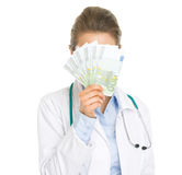 Doctor woman hiding behind fan of euros Stock Images