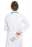 Doctor woman hiding pack of dollars behind back Stock Photography