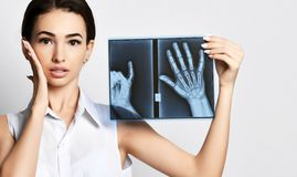 Doctor woman hold hands X-ray examination on gray. Background stock photos