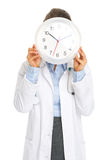 Doctor woman holding clock in front of face Stock Photos