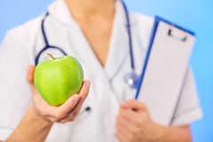 Doctor (woman) holding green apple Stock Photography