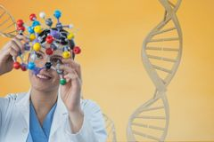 Doctor woman holding a medical figure with 3D DNA strand against yellow background. Digital composite of Doctor woman holding a medical figure with 3D DNA strand Royalty Free Stock Photography
