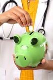 Doctor woman holding a piggy bank Royalty Free Stock Images