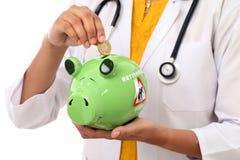 Doctor woman holding a piggy bank Stock Photos