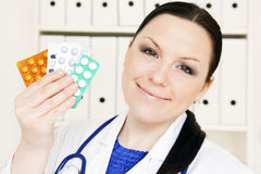 Doctor woman holding pills Stock Image