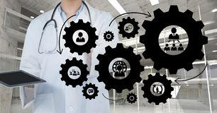 Doctor woman interacting with people in cogs graphics against office background. Digital composite of Doctor woman interacting with people in cogs graphics Royalty Free Stock Image
