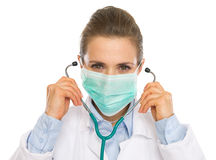 Doctor woman in mask using stethoscope Stock Photo